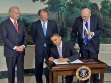 Vice President Joe Biden, Erskine Bowles, UNC System president, and former Republican Sen. Alan Simpson (left to right) stand behind President Barack Obama as he signs an executive order creating a commission charged with finding ways to reduce the federal budget deficit on Thursday, Feb. 17. 2010. Bowles and Simpson will co-chair the commission.
