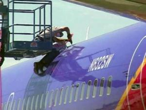 An inspector checks a Southwest Airlines jet on April 4, 2011, for any cracks in the fuselage from metal fatigue.