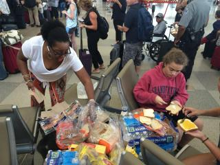 A Triangle woman saw the stranded travelers on TV, went to Sam's Club and bought sandwich supplies, and came to the airport to feed people who didn't want to lose their spot in line.