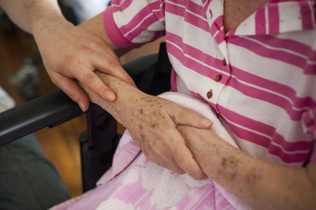 FILE -- Aleks Zeygerman puts his hand on his 87 year-old mother Nelli Leventon's arm, in New York June 3, 2013. The focus on child care may conceal a bigger barrier to female participation in the labor force: tending to the growing ranks of aging family members. (Michael Nagle/The New York Times)