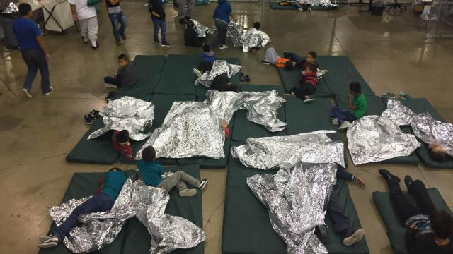 Immigrants are seen here inside a detention center with mattresses and thermal blankets on the floor.