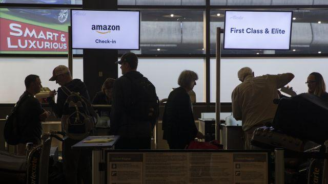 Alaska Airlines agent Oksana Kalvish checks in passengers for their flight at a counter dedicated to Amazon and Microsoft employees at SeaTac airport near Seattle, July 30, 2018. Now, given the nature of travel — crowded planes, tighter seats, security hassles — corporate managers are considering employee comfort as part of the deal. (Ruth Fremson/The New York Times)