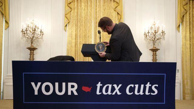 FILE -- A White House staff member attaches the presidential seal marker to a podium ahead of President Donald Trump's remarks celebrating the Tax Cuts and Jobs Act, at the East Room of the White House, in Washington, D.C., on June 29, 2018. American companies could potentially authorize the repurchase of $1 trillion in stock by the end of 2018. (Tom Brenner/The New York Times)