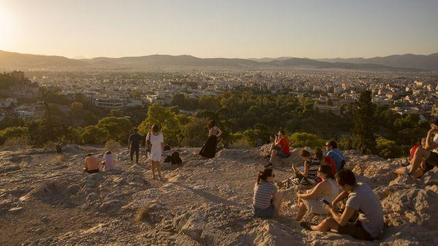 Tourists sit under the Parthenon and watch the sunset over Athens, Greece, Aug. 13, 2018. On Aug. 20, the country will officially end its reliance on over 320 billion euros, or about $360 billion, of bailouts, but after nearly a decade of sharp spending cuts and tax increases, more than a third of the population is in poverty, unemployment remains high, and wages have tumbled. (Eirini Vourloumis/The New York Times)