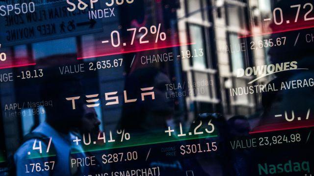 FILE -- Passersby are reflected in a monitor displaying Tesla's information at Nasdaq, in New York, May 2, 2018. The electric-car maker's cash position was closely watched even before its chief executive, Elon Musk, floated the idea of taking the company private. (Jeenah Moon/The New York Times)