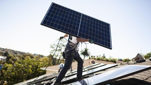 An installer carries a solar panel into place at a customer's home. (Collin Chappelle/The New York Times)