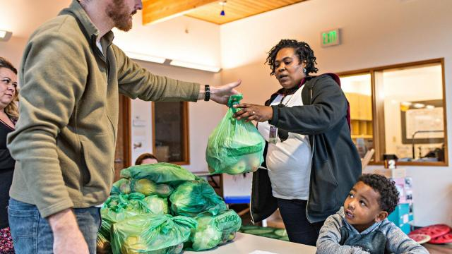 Manny Noriega, 5, looks on while Chris Teeny, left, hands Anisha Noriega a bag of fresh produce at Educare Seattle, Oct. 31, 2018. Coke, PepsiCo and other big beverage companies are the unseen forces (and funders) behind ballot initiatives that would ban taxes on food sales. (Wiqan Ang/The New York Times)