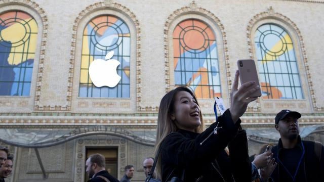 An Apple employee takes a selfie near where an Apple logo hangs on the Brooklyn Academy of Music building, before the company's event in New York, Oct. 30, 2018. Apple's stock plunged on Friday, November 2, 2018, on a disappointing sales forecast. But investors were also unnerved by the decision to stop providing crucial data. (Erica Yoon/The New York Times)