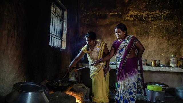 Chain Sahu, right, prepares a meal over a wood fire for election workers at a school in Bhanpuri, India, Nov. 12, 2018. Sahu, who has a government-issued smartphone, said she has received calls urging her to vote for the Bharatiya Janata Party, which subsidizes data plans for residents. The Indian National Congress Party says the move violates laws that prohibit election work by the government. (Atul Loke/The New York Times)
