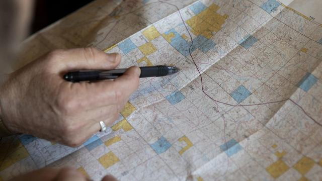 """Karen Aspevig Stevenson looks at a map of lands in and around her cattle ranch near Miles City, Mont., Aug. 28, 2018. The Trump administration is undertaking burst of lease sales on federal lands in the West, much of it in areas where there is little evidence that much oil or gas is easily accessible. """"This is our public lands. We all own this land,"""" Stevenson said. (Kristina Barker/The New York Times)"""