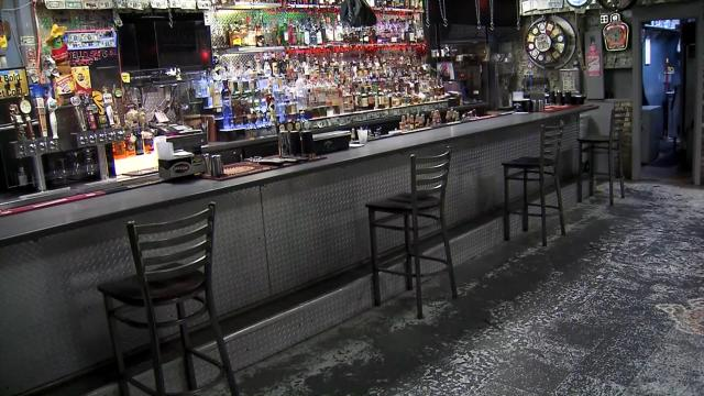 The Goat bar in Raleigh installed plexiglass shield and has hand sanitizer and social distancing signs ready for when it is allowed to reopen during the coronavirus pandemic.