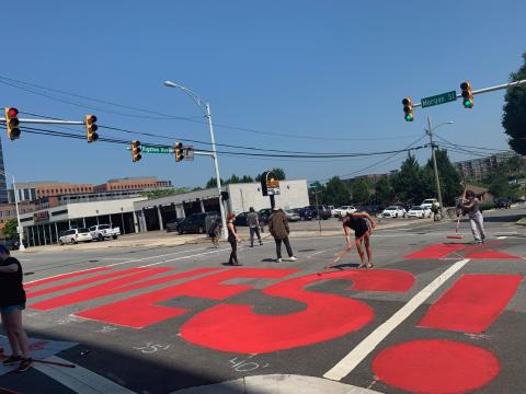 """A group of essential workers paints """"Black Lives Matter"""" at the intersection of Morgan St. and Riggsbee Ave. in Durham"""