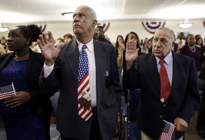 Andre Castillo, of the Dominican Republic, left, and Julio Urbaneja, of Venezuela, right, take the oath of allegiance to become a U.S. citizen during a naturalization ceremony, Friday, Sept. 30, 2016, in Miami. (Deseret Photo)