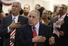 Andre Castillo, of the Dominican Republic, left, and Julio Urbaneja, of Venezuela, right, recite the Pledge of Allegiance during a naturalization ceremony to become a U.S. citizen, Friday, Sept. 30, 2016, in Miami. (AP Photo/Lynne Sladky) (Deseret Photo)
