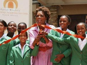 Oprah Winfrey, appearing with young students during a ribbon-cutting ceremony, opens the Oprah Winfrey Leadership Academy for Girls in South Africa on Jan. 2. (AP Photo/Denis Farrell)