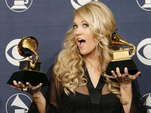 """Carrie Underwood poses with the awards for best new artist and for best female country vocal performance for """"Jesus, Take the Wheel"""" at the 49th Annual Grammy Awards in Los Angeles on, Feb. 11. (AP Photo/Kevork Djansezian)"""