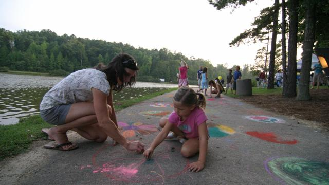 Kayla Akins and daughter Brooke, 5, draw chalk butterflies on the sidewalk at WRAL's Pops in the Park Sunday evening.