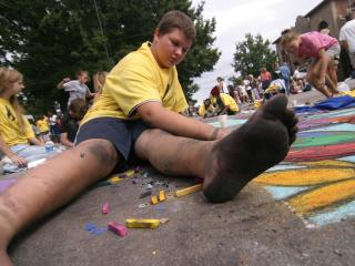 Jake McCraw, 12, applies what chalk is not on his feet to his Martin St. artwork for SparkCon's street painting festival GroundSpark in Moore Square.