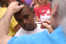 Jaquan Gardner, 12, waits as the last bits of 'blood' are added to the sword on his cheek.