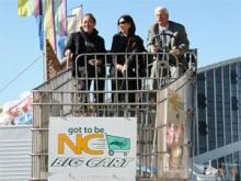 """Ichiro Fujisaki and with state Agriculture Commissioner Steve Troxler take a ride in the """"Got to Be N.C. Big Cart"""" at the State Fair on Oct. 19, 2008. (Image from the state Department of Agriculture)"""