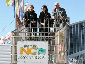 "Ichiro Fujisaki and with state Agriculture Commissioner Steve Troxler take a ride in the ""Got to Be N.C. Big Cart"" at the State Fair on Oct. 19, 2008. (Image from the state Department of Agriculture)"