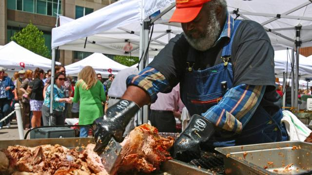 The Pitmaster Ed Mitchell chops up barbecue for a long line of people at the State Farmer's Market in 2010.