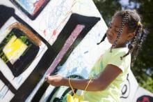 "Ella Smith draws on a coloring wall in Moore Square during Artsplosure Saturday afternoon. ""It's fun to be creative,"" Smith said. (Photo credit: Matt Moore)"