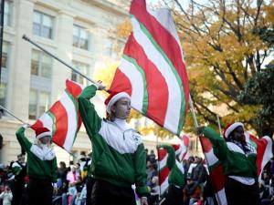 The colorguard of the Cary High School Marching Band twirl their flags in sync to a Jingle Bell Medley.  Santa Claus made his guest appearance behind the Cary High School Marching Band
