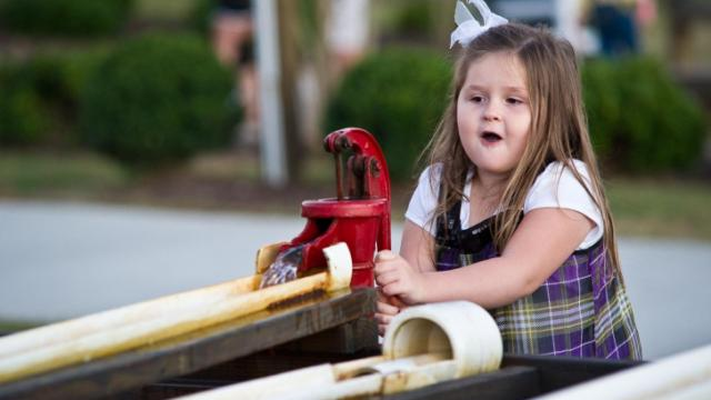 Four-year-old Ally pumps water to make her duck race down the trough at Hill Ridge Farms in Youngsville on Oct. 15, 2011.