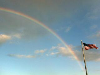 A rainbow forms behind an American flag flying in Southport, N.C. on Sunday, May 27, 2012. (Photo courtesy of Sarah Maness)