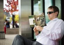 A commuter waits for public transportation while enjoying the new pocket edition of the Pathfinder RPG Bestiary as seen in Salt Lake City, Thursday, Oct. 27, 2016. (Deseret Photo)