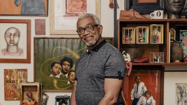 """Patric McCoy in front of a painting by his father, """"Nuclear Family"""" (1954) in his apartment in Chicago, July 3, 2018. McCoy, an enthusiastic art buyer, has some 1,300 paintings, sculptures and drawings stuffed into his Chicago apartment. (Whitten Sabbatini/The New York Times)"""