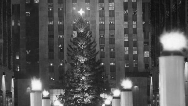 "FILE -- A double row of candles lines the walkway to the Rockefeller Center Christmas tree in New York, 1939. A 1939 New York Times article describes the tree: ""It is the biggest set up there since the custom was started and will stand undecorated except for the floodlights now being connected and the silvery gleam of a gigantic star in its topmost branches."" (The New York Times)"