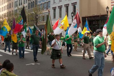 Holding flags from Irish decent, these St. Patrick's Day Parade participants celebrate their heritage with parade attendees.