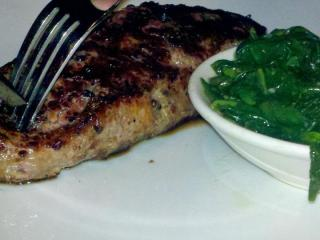 A crusty exterior and sauteed greens accentuate the juicy steak.