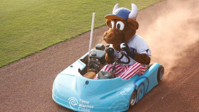 Wool E Bull tosses balls to fans from his kart during a Durham Bulls game on July 4, 2012 in Durham, NC.