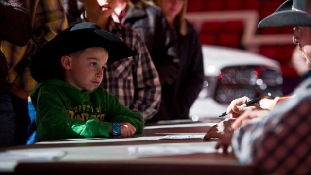 Fans get autographs from the cowboys before the action begins during the World's Toughest Rodeo at the PNC Arena in Raleigh, NC on January 19, 2013.