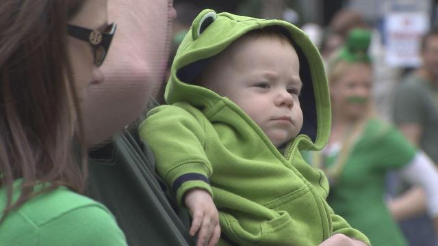 A baby attired in green enjoys the St. Patrick's Day parade in Raleigh.