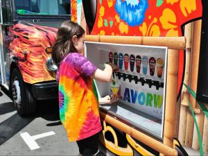 A girl flavors her own snow cone during the Downtown Raleigh Food Truck Rodeo.