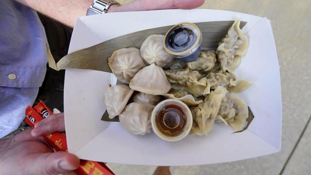 A plate of dumplings from Chirba Chirba Dumplings is carried through the crowd during the DBAP Food Truck Fest at the Durham Bulls Athletic Park Wednesday, July 10, 2013 in Durham, NC.
