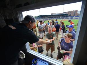 A customer is handing his sandwich at American Meltdown during the DBAP Food Truck Fest at the Durham Bulls Athletic Park Wednesday, July 10, 2013 in Durham, NC.