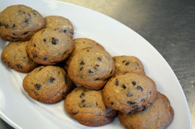 Fresh chocolate chip cookies cool on a plate in the kitchen.