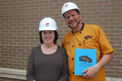 Tupelo Honey Cafe chef Brian Sonoskus and Elizabeth Sims hold up their latest cookbook outside of the location of their future Raleigh location.