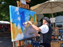 Dan Nelson creates a painting during Artsplosure in Raleigh on Saturday, May 17, 2014. Photo by Christine Adamczyk.