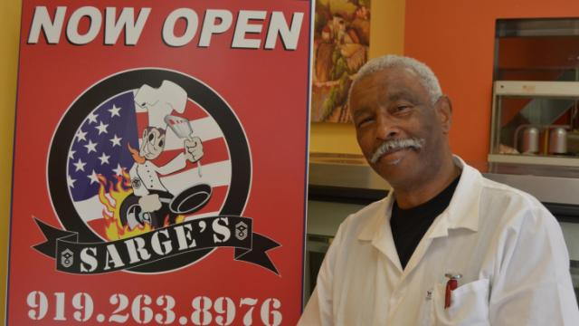 Sarge's Julius West stands next to the sign for his new brick-and-mortar restaurant in Rolesville.