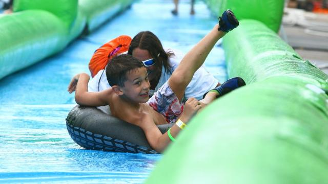 "Sliders coast down Glenwood Avenue to try to beat the heat at the ""Slide the City"" water Party. The ""Slide the City"" water party was held on Glenwood Avenue in Raleigh, North Carolina on May 30, 2015. (Photo by: Jerome Carpenter\WRAL Contributor)"