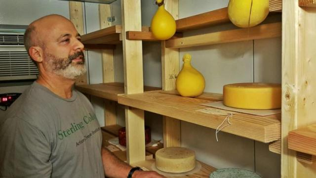"Richard Nathan stands in his ""cheese cave,"" where cheeses age in his Raleigh home."