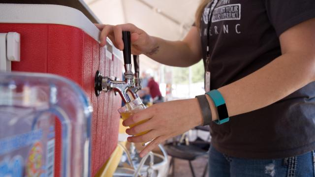 An employee from Brice's Breaing Company in Garner pours a sample of its Honey Lavender Saison on Saturday at World Beer Festival in Raleigh.