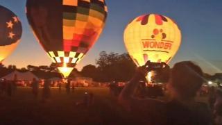 Spectators cheer as balloons glow
