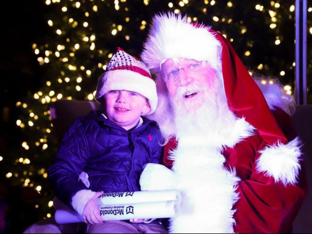 A young boy poses for a picture with Santa Claus. The Annual Christmas Tree Lighting Celebration was held in the Commons of North Hills in Raleigh, NC on November 23, 2019 (Jerome Carpenter/WRAL Contributor)<br/>Photographer: Jerome  Carpenter